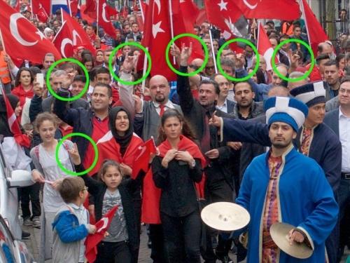 Dat handgebaar is het teken van de Grijze Wolven, een Turkse neo nazi club, vergelijkbaar met de Hitlergroet,