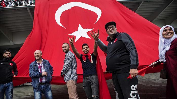 Dat teken dat deze Turken met hun handen maken is dat van de Grijze Wolven, een extreem rechtse fascistische club.